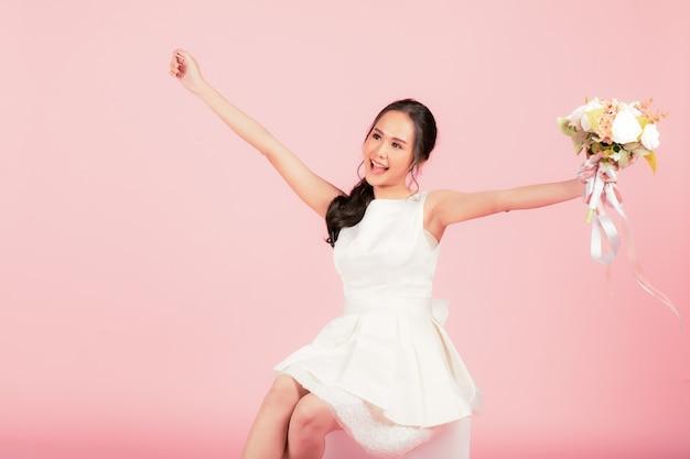 ピンクの背景に幸せで陽気に見える花の花束を保持している白いウェディングドレスを着ている若い魅力的なアジアの女性。結婚式前の写真撮影のコンセプト。