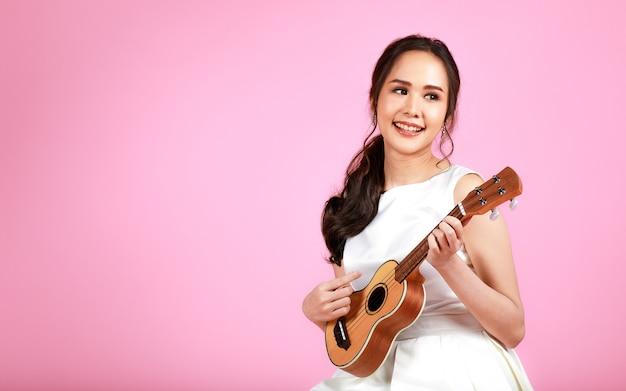 ピンクの背景に幸せで陽気に見えるウクレレを演奏する白いウェディングドレスを着ている若い魅力的なアジアの女性。結婚式前の写真撮影のコンセプト。