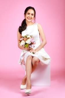 ピンクの背景に花の花束を持って座って白いウェディングドレスを着ている若い魅力的なアジアの女性。結婚式前の写真撮影のコンセプト。