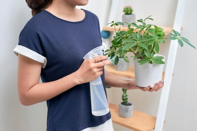 植物に水を与える若い魅力的なアジアの女性