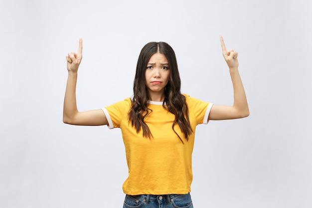 不幸な感情で指を指す若い魅力的なアジアの女性