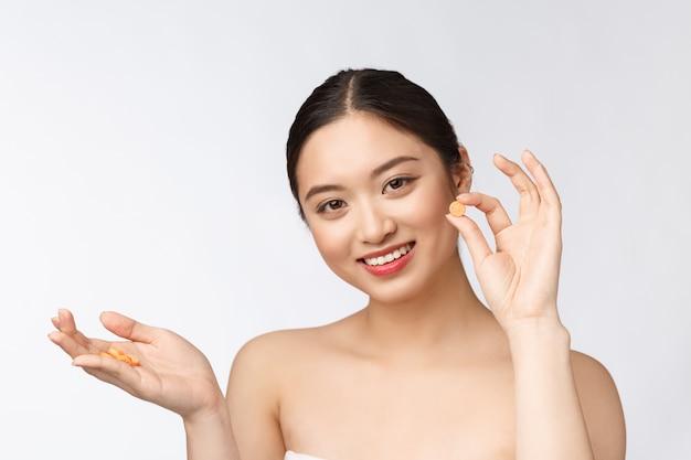 Молодая привлекательная азиатская женщина которая принимает капсулу или пилюльку изолированную сверх