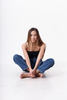 검은 탑, 청바지 흰색 스튜디오 배경에 고립에 긴 머리를 가진 젊은 매력적인 아시아 여자. 다리를 건너 cyclorama에 앉아 마른 예쁜 여성. 아름다운 여인의 모델 테스트