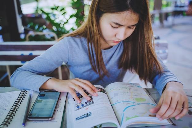 若い魅力的なアジアの女性がホリデーを計画するためにスマートフォンと旅行ブックを使用しています