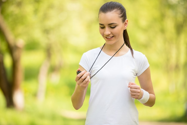 Young attractive athletic girl holding stopwatch.