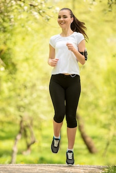 Young attractive athletic girl jogging at park in morning.