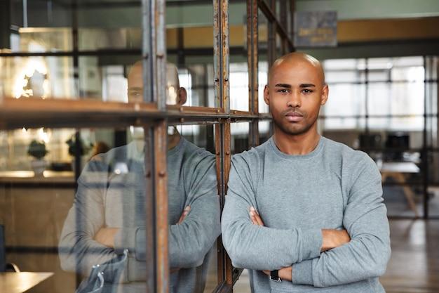 Молодой привлекательный лысый афро-американский мужчина, стоящий со скрещенными руками во время работы в офисе