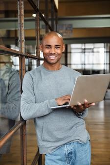Молодой привлекательный лысый афро-американский мужчина в толстовке держит портативный компьютер во время работы в офисе