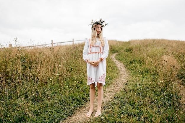フィールドでポーズをとって頭に飾りと花の花輪と白いドレスを着た若い魅力的な裸足のブロンドの女の子