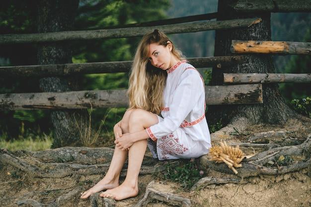 야외 나무 울타리 근처에 앉아 장식으로 흰 드레스에 젊은 매력적인 맨발 금발 소녀