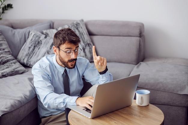 Молодой привлекательный бородатый бизнесмен сидит на полу дома, используя ноутбук и имея представление о том, как решить проблему.