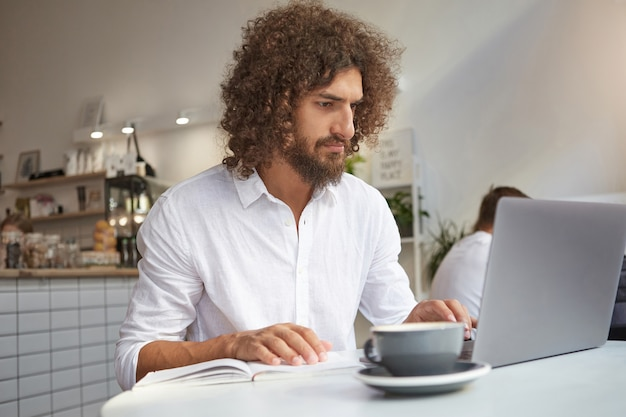 Young attractive bearded businessman working out of office with his working notes and modern laptop, using public wi-fi in coffee shop, concentrated on his job