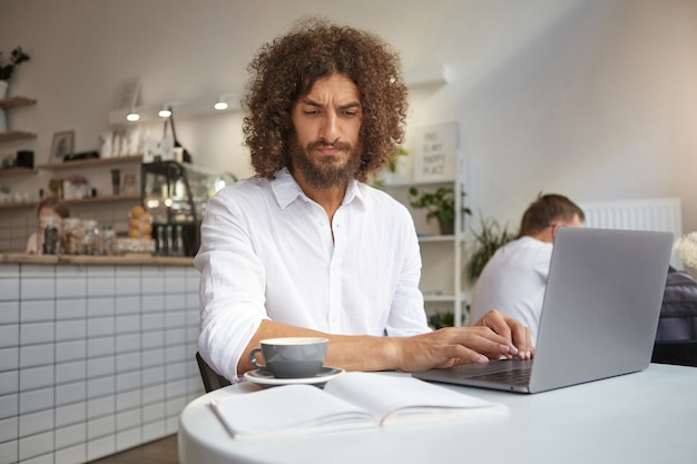 Young attractive bearded businessman working remotely in cafe with modern laptop, keeping hands on keyboard and looking intently in his notes