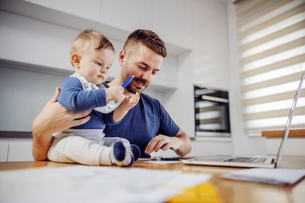 若い魅力的なひげを生やした父親は、愛する愛らしい息子と一緒にダイニングテーブルに座って、オンラインで請求書を支払います。ペンを持って助けようとした少年。