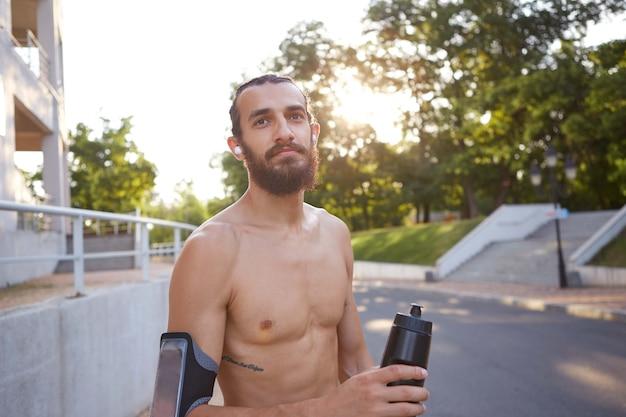 Молодой привлекательный бородатый парень занимается экстремальным спортом в парке, держит бутылку с водой, ведет здоровый активный образ жизни. мужская модель фитнеса.