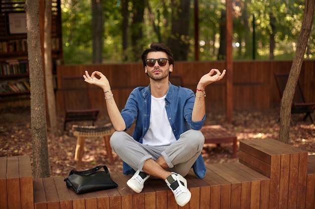 足を組んで都市公園に座っている若い魅力的なひげを生やした男性、ムードラジェスチャーで手を上げる、瞑想しながら落ち着いて、カジュアルな服を着て
