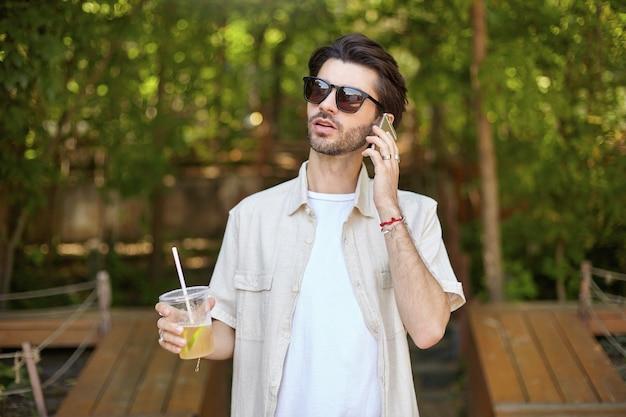 Giovane uomo barbuto attraente in camicia beige e occhiali da sole che effettua una chiamata con il suo telefono cellulare, passeggiando per la città verde prk con limonata in mano