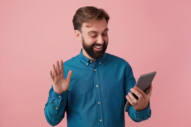 デニムシャツを着て、笑顔で手を振って、ビデオチャットで妹と話している若い魅力的なひげを生やした男。ピンクの背景に分離。