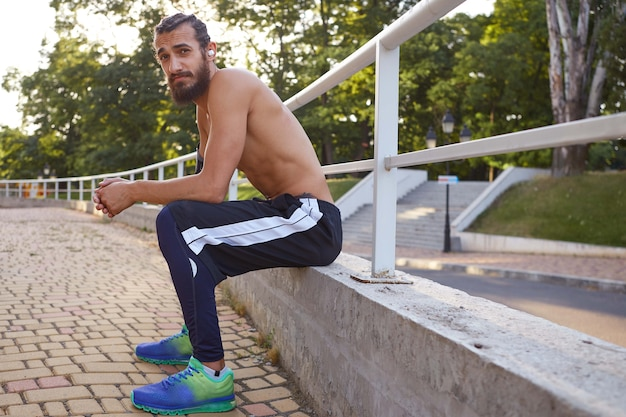 Young attractive bearded man has extreme sport in park, rest at the park after jogging, looks at the camera.