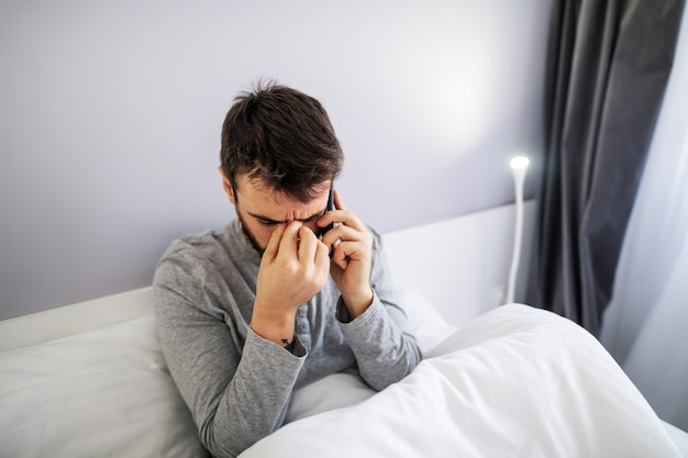 Young attractive bearded man sitting on the bed in the morning and having unpleasant phone call