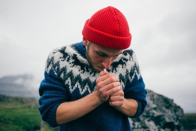 赤い漁師または船乗りのビーニー帽子と伝統的なアイスランドの装飾品の青いセーターの若い魅力的なひげを生やしたミレニアル世代の男