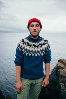 Giovane uomo millenario barbuto attraente in cappello rosso pescatore o marinaio beanie e maglione blu ornamento tradizionale islandese