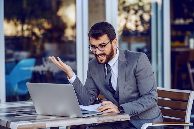 若い魅力的なひげを生やした笑みを浮かべて白人実業家の議題でタスクを書いてラップトップを見てします。カフェ外観。 Premium写真