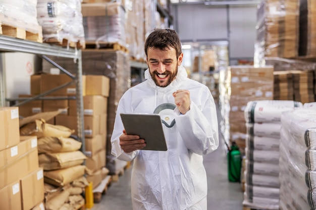 Young attractive bearded smiling supervisor in protective uniform standing in warehouse