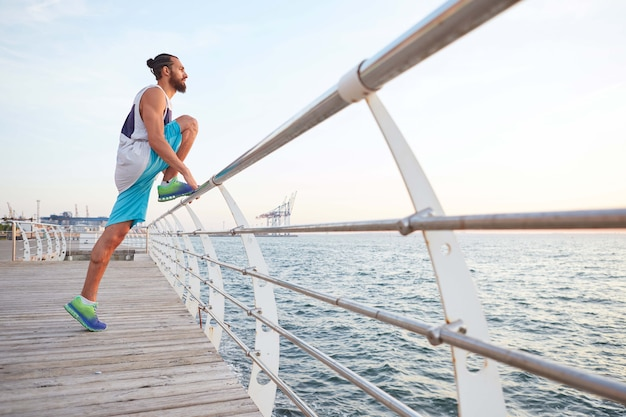 Young attractive bearded sporty guy doing morning exercises by the sea, stretching for legs, warm-up after run, leads healthy active lifestyle. fitness male model.