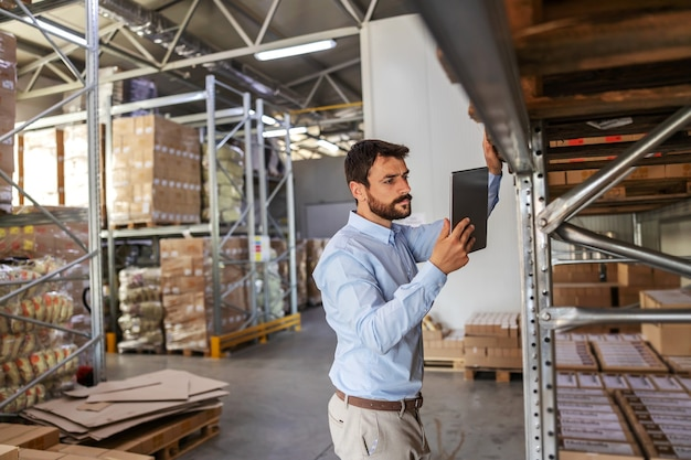 Young attractive bearded supervisor standing next to shelves in warehouse and checking on goods while holding and looking at tablet.