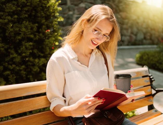 야외 벤치에 앉아있는 동안 책을 읽고 젊은 매력적인 금발 여성 학생 학생