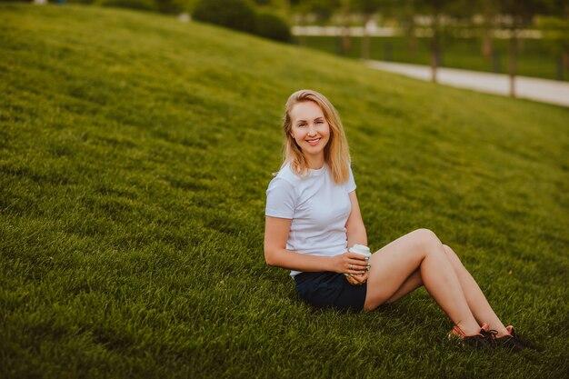 公園の緑の芝生の上に座ってコーヒーを保持している白いシャツとショートパンツの若い魅力的なブロンドの髪の女性。スペースをコピーします。