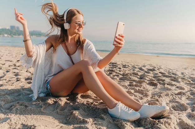 Молодая привлекательная блондинка улыбается женщина, делающая селфи фото по телефону в отпуске, сидя на пляже
