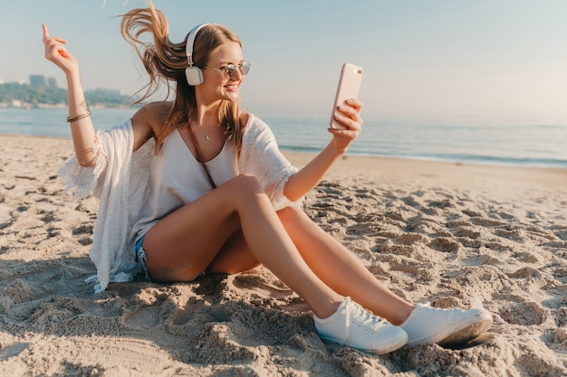 Giovane donna sorridente bionda attraente che prende la foto del selfie sul telefono in vacanza che si siede sulla spiaggia