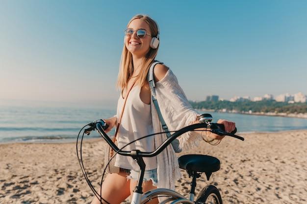 음악을 듣고 헤드폰에 자전거와 함께 해변에 산책하는 젊은 매력적인 금발 웃는 여자