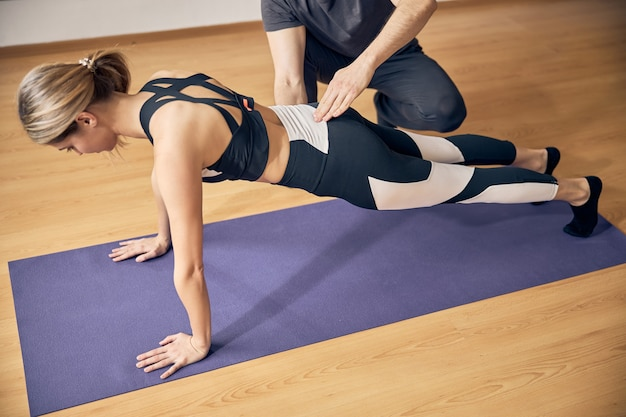 Young attractive blond with fit body working out in yoga class while experienced instructor helping her