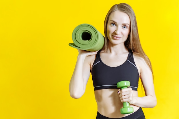 Young attractive blond woman holding a mat and a dumbbell on yellow