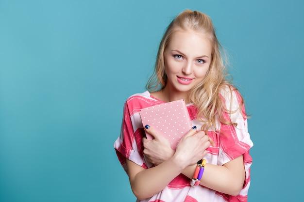 青い背景にピンクの本を保持している若い魅力的な金髪の女性