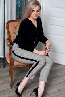 Бизнес-леди молодой привлекательной белокурой женщины нося сидя на стуле
