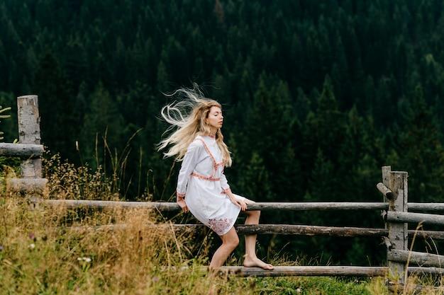 그림 같은 숲 풍경 위에 나무 울타리에 앉아 자수와 흰 드레스에 젊은 매력적인 금발 소녀