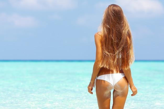 열대 여름 해변에서 비키니 입은 완벽한 스포츠 몸매를 가진 젊은 매력적인 금발 소녀