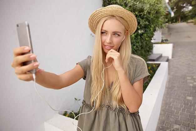 Giovane donna bionda attraente che fa selfie con il suo smartphone, guardando alla fotocamera del telefono delicatamente e toccando il mento con la mano, indossando abiti di lino casual e cappello di paglia