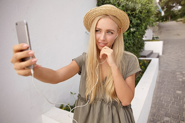 スマートフォンで自分撮りをし、カメラ付き携帯電話を優しく見つめ、手で顎に触れ、カジュアルなリネンのドレスと麦わら帽子を身に着けている若い魅力的な金髪の女性