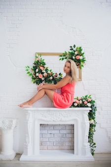 Young attractive blonde woman near christmas fireplace in cosiness home interior. teenage girl in red dress. winter holidays concept. white beautiful decor