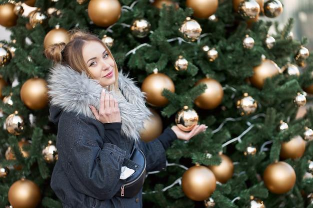 골든 볼 크리스마스 트리의 배경에 포즈 젊은 매력적인 금발 여자.