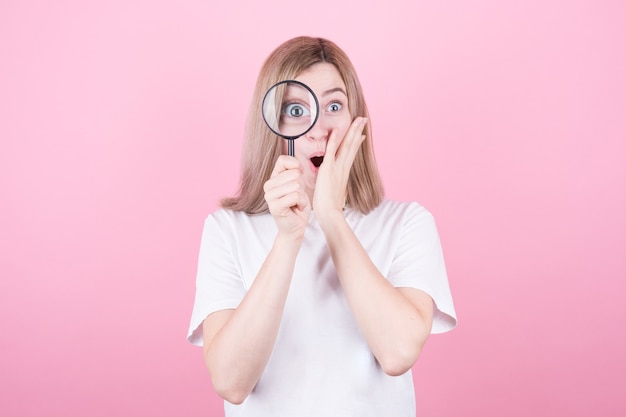 Young attractive blonde woman shocked while looking through a magnifying glass over pink wall
