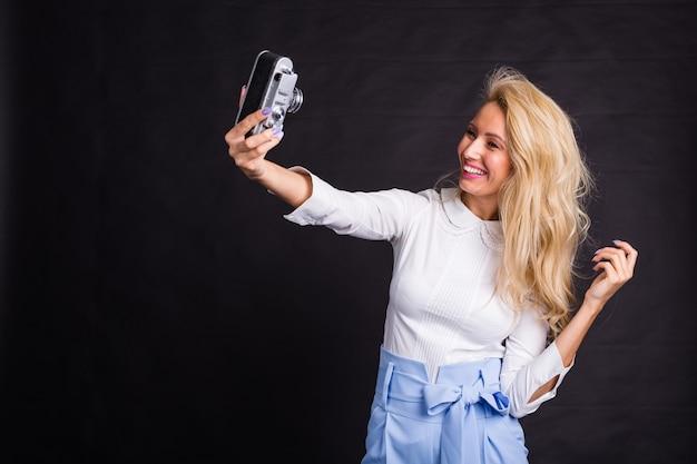 黒い表面のビンテージカメラでselfieを取っている若い魅力的なブロンドの女性。