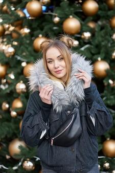 골든 볼 크리스마스 트리 배경에 세련 된 데님 재킷을 입고 젊은 매력적인 금발 여자.