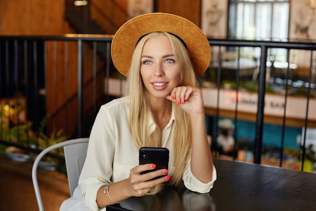 Молодая привлекательная белокурая женщина с длинными волосами сидит за столиком в кафе и мечтательно смотрит вперед, трогая свою ци и держа смартфон