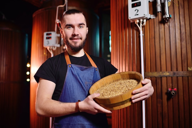 Young attractive brewer enjoys the aroma of malt on the surface of the brewery and beer tanks